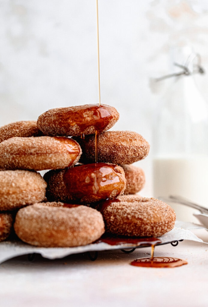 Homemade baked apple cider donuts are the perfect fall treat. Covered in browned butter and cinnamon sugar and topped with warm maple.