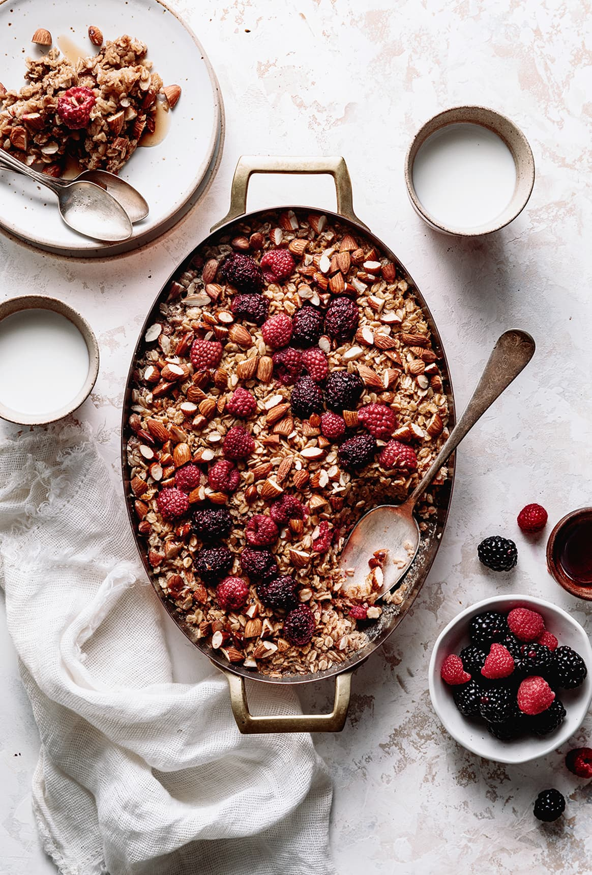 Warm Almond and Berries Baked Oatmeal sweetened with maple and brown sugar and topped with fresh berries. A cozy breakfast casserole for the whole family!