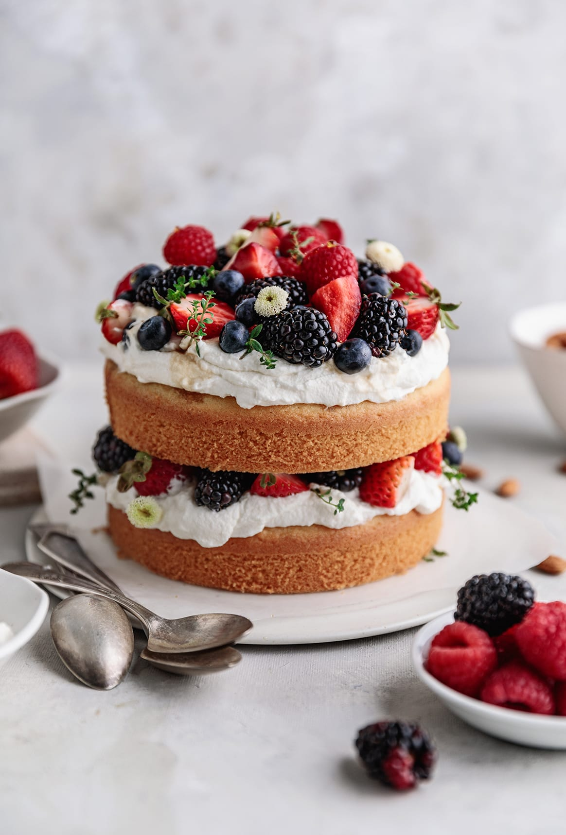layered almond cake with whipped cream and berries