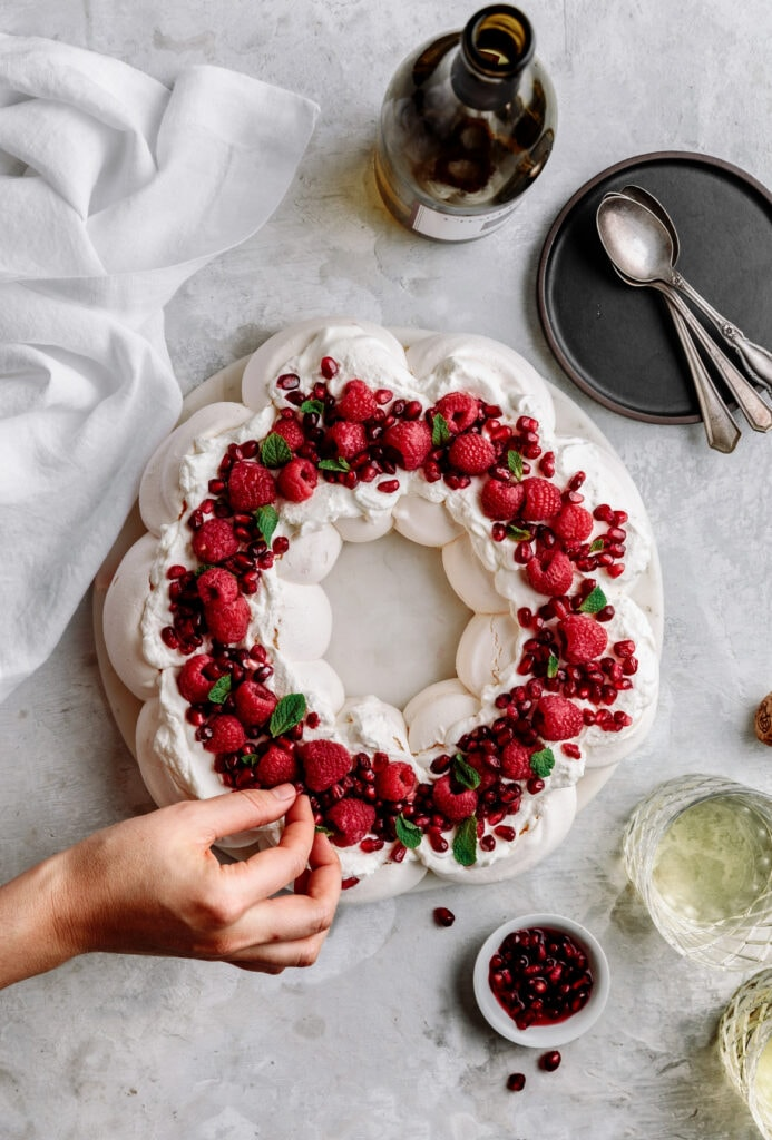A delicate and crunchy shell with a marshmallowy center, this Pavlova Wreath with Almond Cream and Raspberries is the most beautiful holiday dessert you'll ever make!