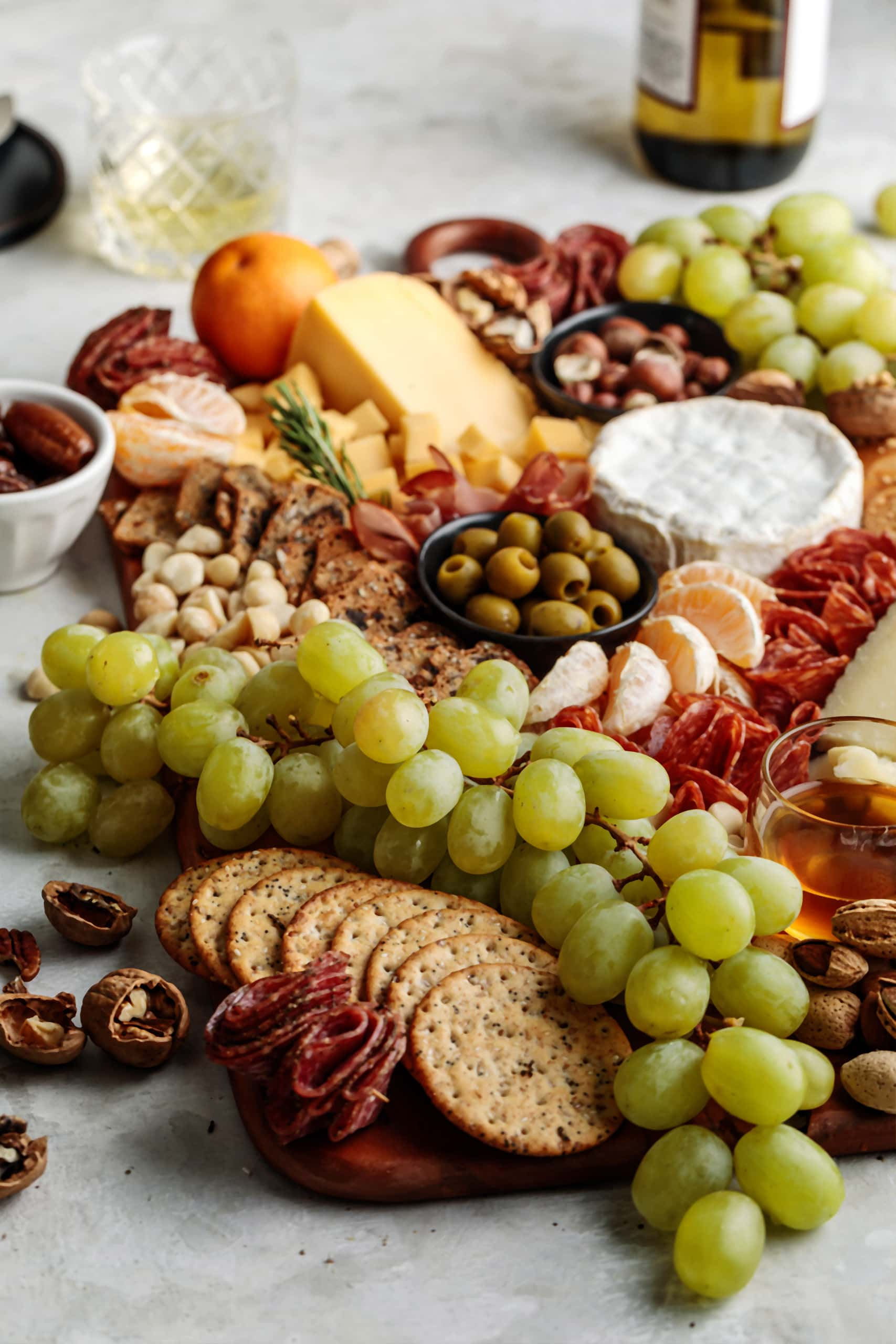How to build an easy and impressive Winter Cheese Board featuring seasonal fruits, nuts, olives and a variety of cheese and charcuterie.