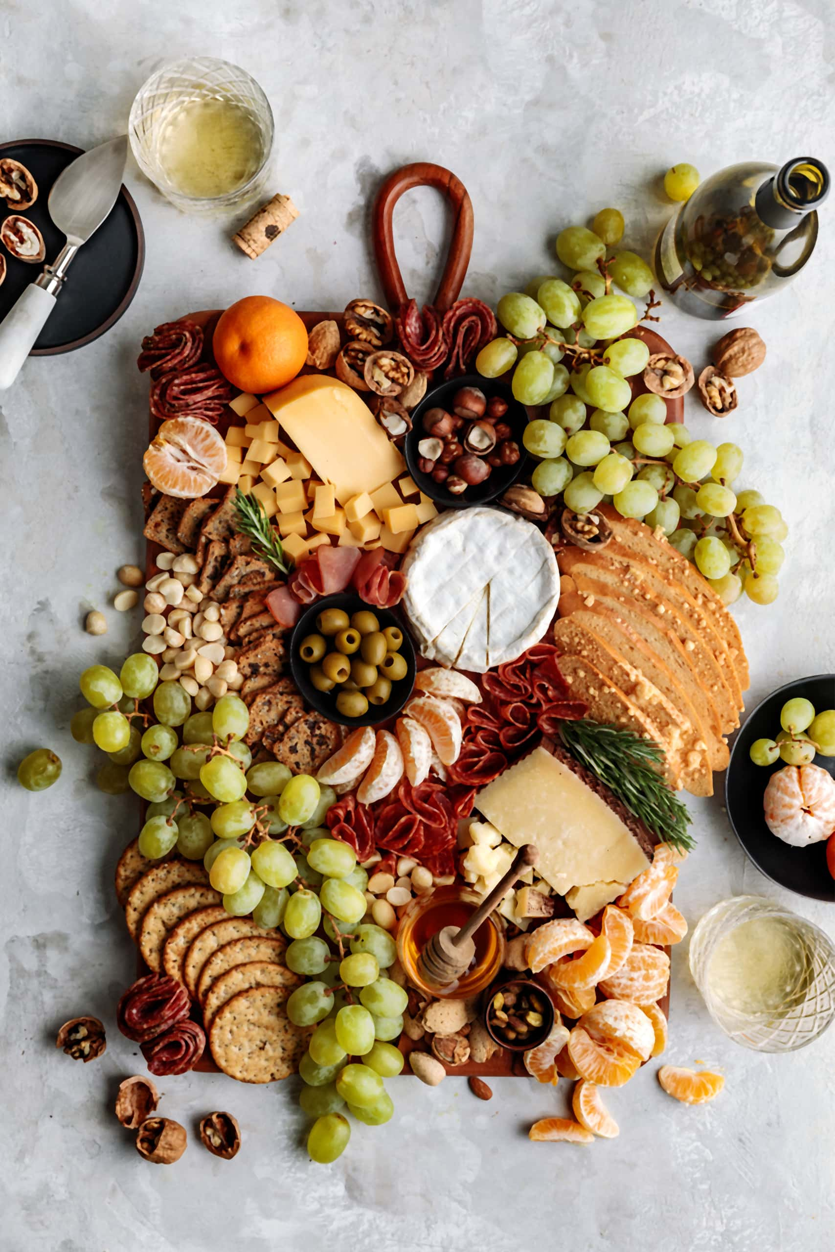 Easy and impressive Winter Cheese Board featuring seasonal fruits, nuts, olives and a variety of cheese and charcuterie.