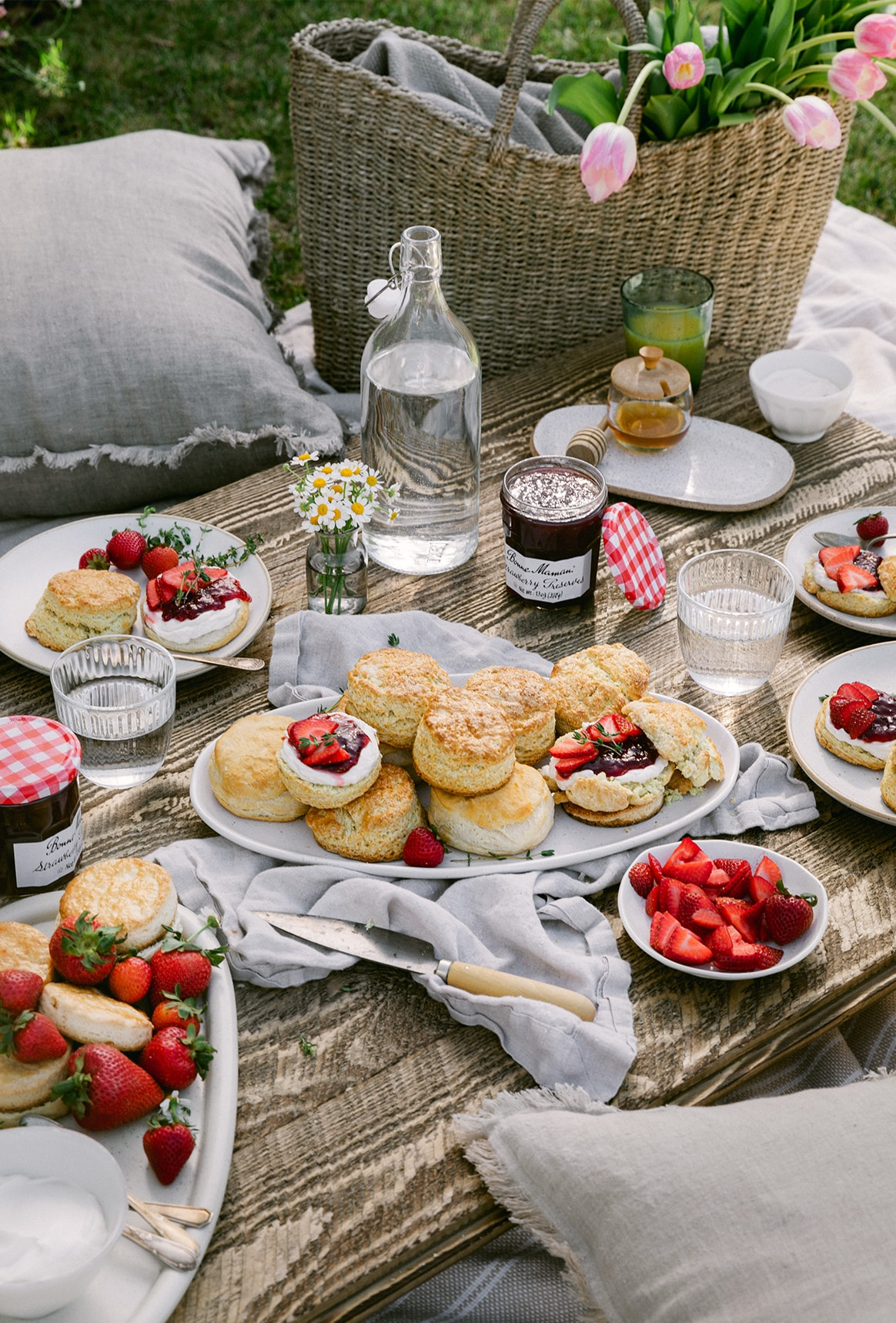 Spring picnic setting with strawberry shortcakes filled with whipped labneh and preserves.
