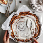 Apple cinnamon roll cake on skillet with icing